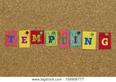Tempting word written on colorful sticky notes pinned on cork board.