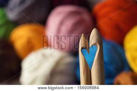 wooden knitting needles on background of colorful merino wool balls heart symbol