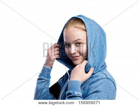 Teenage girl in blue sweatshirt, wearing phone armband, holding hood. Beautiful young sportswoman, studio shot on white background, isolated.