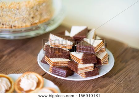 Close up, chocolate waffers and tarts filled with jam decorated with vanilla cream laid on plate. Studio shot. Wooden table backround.