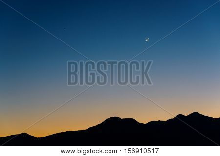 Waxing crescent Moon, Venus (left) and Saturn (middle) at dusk. Silhouette of mountains near Kathmandu in Nepal.