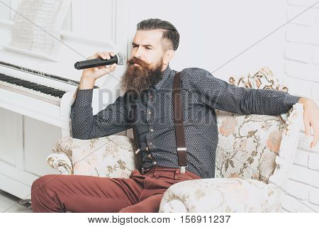 Handsome bearded young man in fashionable shirt and pants sit on luxurious baroque decorated with flowers armchair near white piano singing in mic or microphone