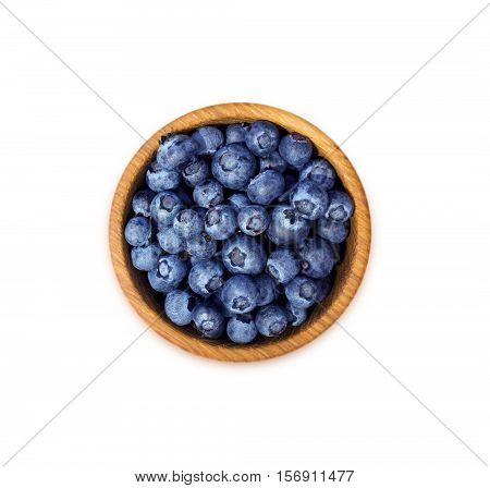 Blueberries in a wooden bowl. Top view. Ripe and tasty blueberries isolated on white background.