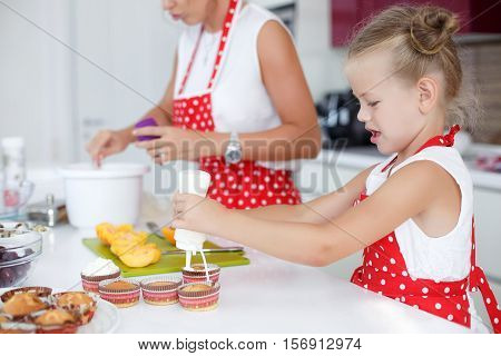 Young woman,brunette,hair gathered on the crown,dressed in a white shirt and a red apron with white polka dots,with my daughter 5 years old,a little blond girl in white tank top and a red apron with white polka dots baking cupcakes in the kitchen