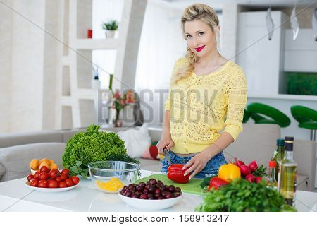 Young, beautiful, slender woman,housewife,blonde with blue eyes,light makeup,bright red lipstick,wearing jewelry,wearing a yellow blouse and blue jeans,is in the large bright kitchen is slicing vegetables for the preparation of dietary salad