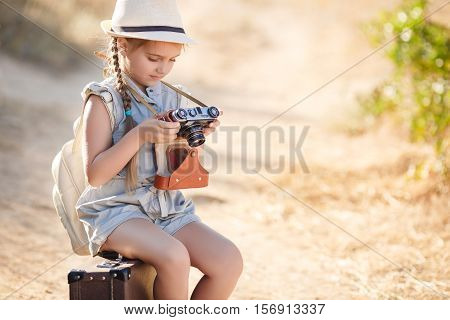 Little girl 6 years old brown suitcase and an old camera in his hands,brunette with two braids,a straw hat from the sun,in a blue summer suit,pictures of nature while traveling,sitting on a suitcase on country road