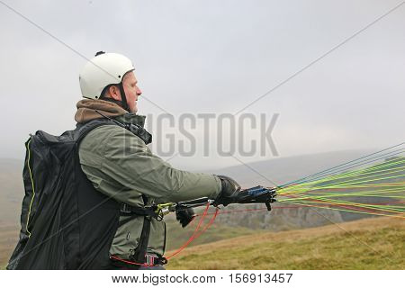 Paraglider launching his wing on the Brecon Beacons