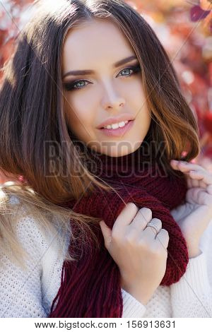 Beautiful young woman in white knitted sweater,round neck wears a maroon knitted scarf,brunette,long straight hair,gray eyes,pink lipstick and light makeup posing in autumn Park on a background of red,yellow and green leaves,portrait in autumn Park
