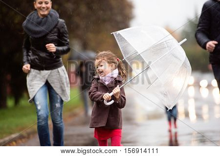 Little girl under the umbrella with her beautiful family, running. Walk on a rainy day.