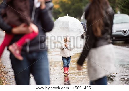 Little girl under the umbrella on a walk with her beautiful family. Autumn rainy day.