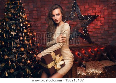Sexy Woman With A Big Christmas Present. Beautiful Girl In A Short Dress Sitting On The Sofa
