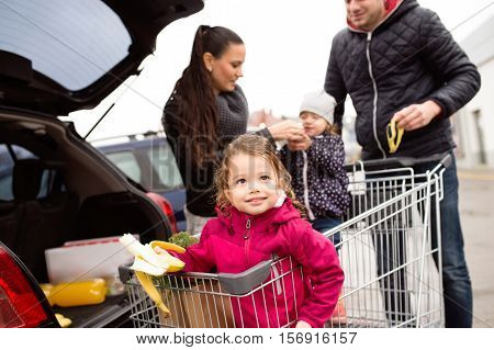 Young parents unloading groceries from shopping cart to the back of the car. Two little daughters sitting in a trolley, eating babanas. Autumn rainy day.