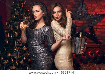 Two Blonde And Dark Hair Girls With  Bottle Of Champagne On A Christmas Party Dancing Together! This