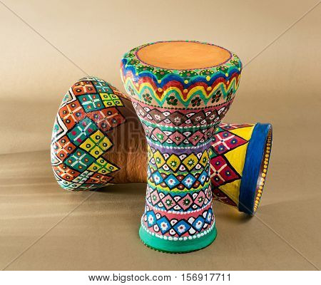 Two decorated colorful pottery goblet drums (chalice drum tarabuka darbuka) on background of wooden table with vanishing shadow lines