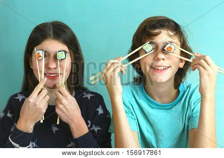 teen siblings boy and girl kids with sushi rolls avocado and salmon close up smiling photo brother and sister eating sushi rolls