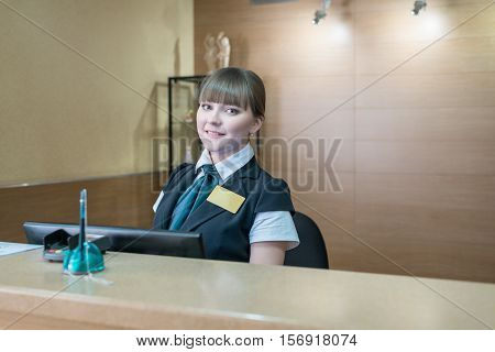 Hotel reception. Image of pretty hostess smiling at camera