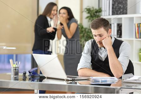 Two coworkers bullying a worried colleague that is sitting in his workplace at office