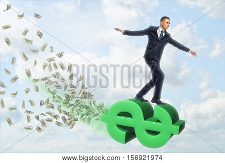 Businessman flying on a large dollar sign with dollar bills on a sky background. Waste money. Millionaire and billionaire. Have large cash income. Profit growth.