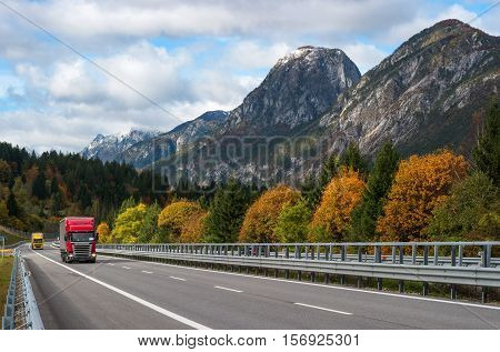 Red truck driving on the highway in the Alps. View of the mountains and yellow autumn trees. poster