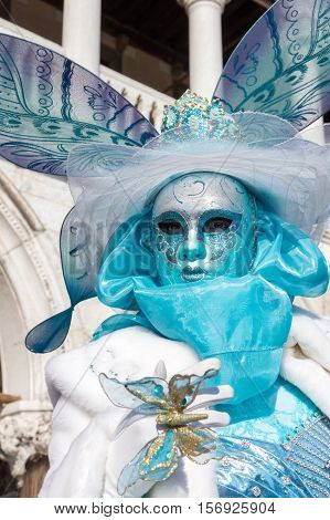 VENICE, ITALY - FEBRUARY 16, 2015: An unidentified woman in a turquoise and white carnival costume, posing at the Carnival of Venice