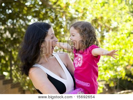 Mother and daughter laughing and playing
