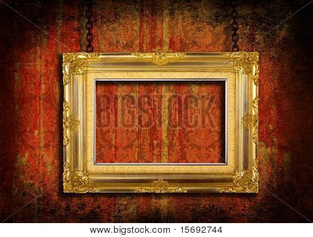 A gold frame held with chains on a grungy velvet background