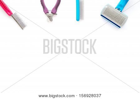 Cat and small dog grooming tools: fine toothed comb wide toothed comb slicker brush and small nail clipper isolated on white background.