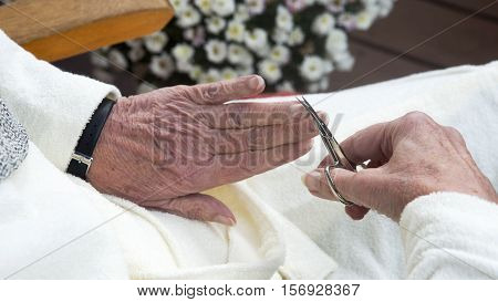closeup of old wrinkled female hands cutting fingernail with scissors