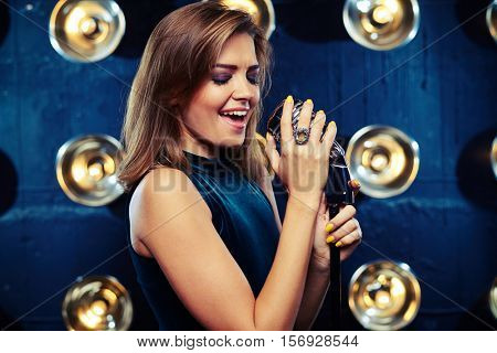 Emotional vocally talented artists slowly caress a retro vintage shiny microphone on spotlights blurred background, mid side view shot