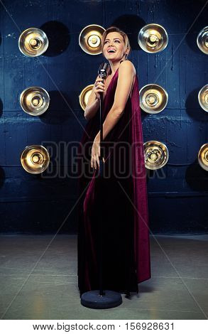 Live performance of exhilarated young female singer in vinous dress smiling while holding silver vintage microphone; mid pin up shot. Singing woman with retro microphone. Glamour singer girl
