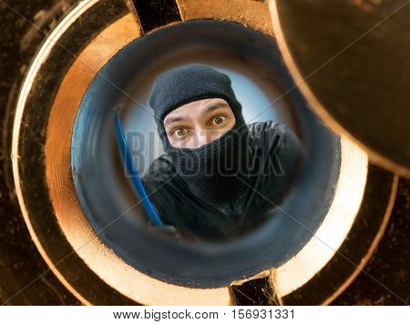 View Through Pipehole. Robber Or Burglar Masked With Balaclava B