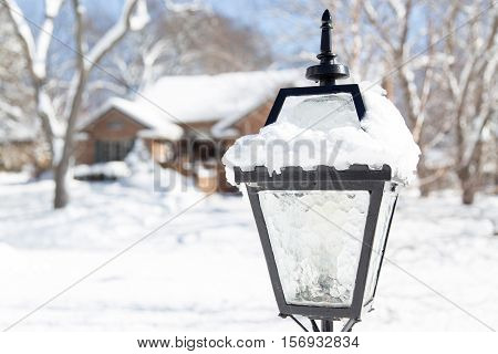 coach style lightpost in focus against a suburban neighborhood under a blanket of winter snow