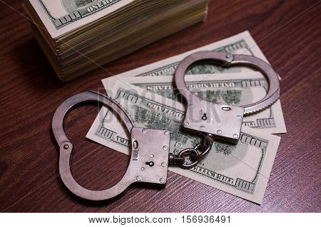 money and the law handcuffs on money 100 dollar bills back side and handcuffs. background of dollars savings taxes and law