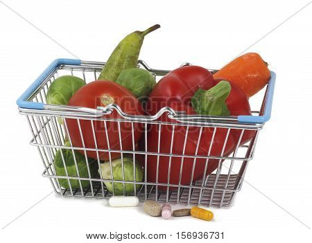 Health Supplements plus Fruit and Vegetables - a small shopping basket containing healthy fresh fruit and vegetables and five different health supplements beside on a white background