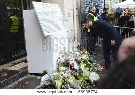 Paris, France - November 13, 2016: Young man posing a flower in front of the memorial for the anniversary of the Bataclan attack