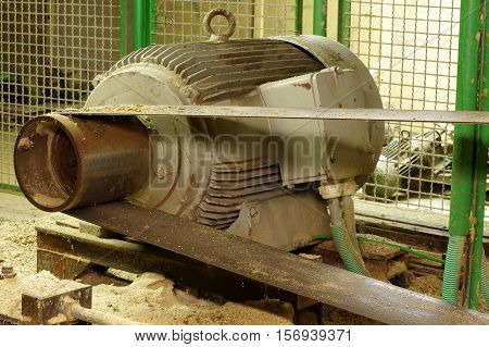 Electric motor belt drive sawmill wood industry theme.
