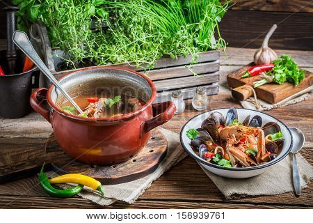 Seafood Soup With Langoustines And Mussels On Old Wooden Table