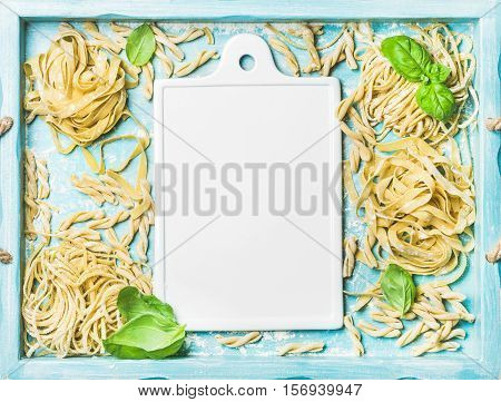 Various homemade fresh uncooked Italian pasta with flour and green basil leaves in blue wooden tray with white ceramic board in center, top view, copy space, horizontal composition
