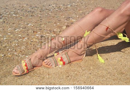 model advertises bohemian greek sandals at the beach - summer shoes advertisement