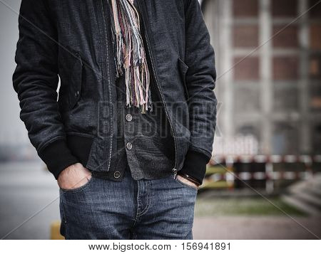 Autumn fashion. Closeup young man wearing cardigan jacket and denim jeans standing with his hands in the pockets outdoors