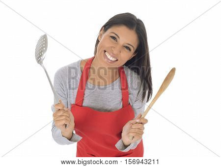 corporate portrait of young attractive hispanic home cook woman in red apron posing happy and smiling holding spoon and skimmer isolated on white background in chef and successful cooking