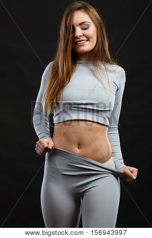 Fit fitness slim woman wearing hot gray sports thermolinen underwear studio shot on black. Long sleeves top and leggings.