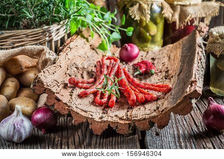 Smoked Thin Sausages In Rural Storeroom On Bark