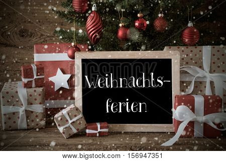 Nostalgic Christmas Card For Seasons Greetings. Christmas Tree With Balls And Snowflakes. Gifts In The Front Of Wooden Background. Chalkboard With German Text Weihnachtsferien Means Christmas Holidays