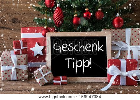 Chalkboard With German Text Geschenk Tipp Means Gift Tip. Colorful Card For Seasons Greetings. Christmas Tree With Balls And Snowflakes. Gifts Or Presents In The Front Of Wooden Background.