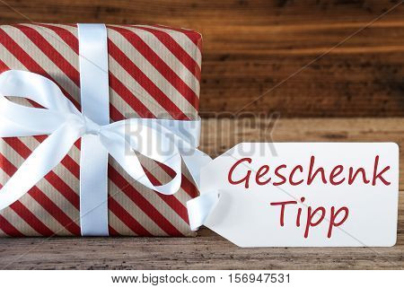 German Text Geschenk Tipp Means Gift Tip. Macro Of Christmas Gift Or Present On Wooden Background. Card For Seasons Greetings, Best Wishes Or Congratulations. White Ribbon With Bow.