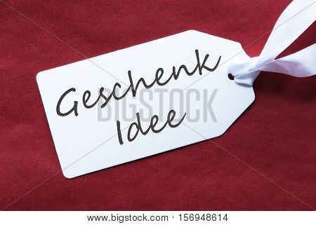 German Text Geschenk Idee Means Gift Idea. One White Label On A Red Textured Background. Tag With Ribbon.