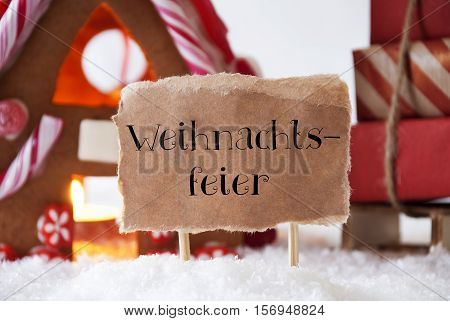Label With German Text Weihnachtsfeier Means Christmas Party. Gingerbread House In Snowy Scenery As Christmas Decoration. Sleigh With Christmas Gifts Or Presents.