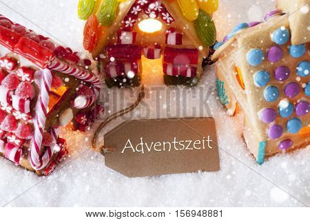 Label With German Text Adventszeit Means Advent Season. Colorful Gingerbread House On Snow And Snowflakes. Christmas Card For Seasons Greetings