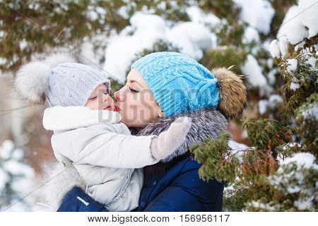 Mother and young daughter embracing in a winter park. Mother and daughter in her arms. Happy family. Childhood and parenthood happiness. Strong hugs and kisses.